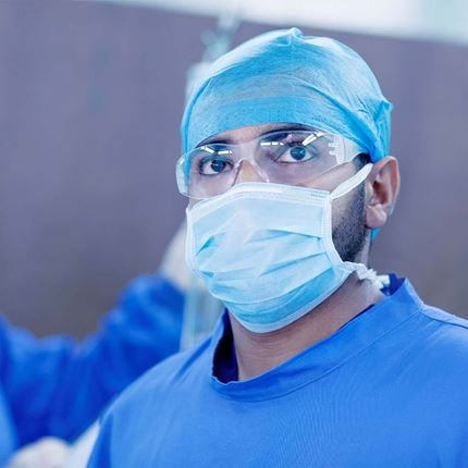 Doctor looking upward to monitor in hospital operating room.