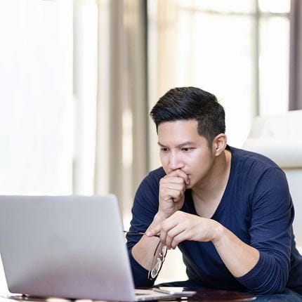 Confident young man in smart casual working and concentrated on a laptop computer sitting on a desk in modern office.