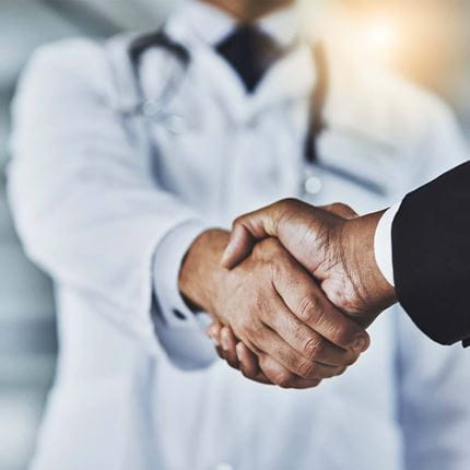 Cropped shot of a doctor shaking hands with a businessman in a hospital.